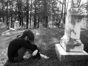 1413340-a-grieving-girl-mourns-in-a-graveyard-curled-up-in-front-of-a-large-grave